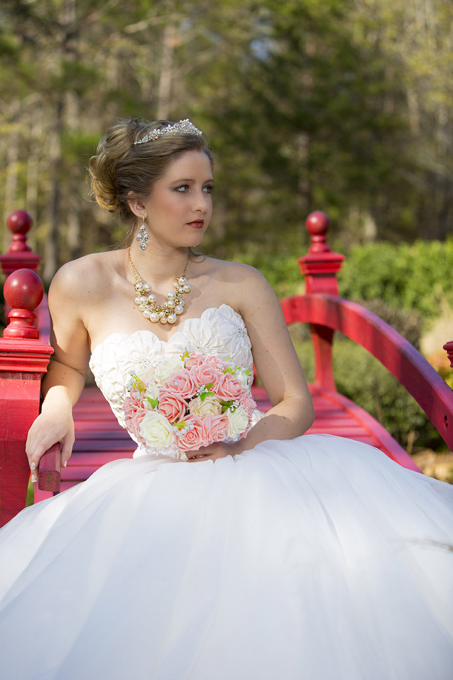 bride posing on a bridge with trees in background and flowers in hand