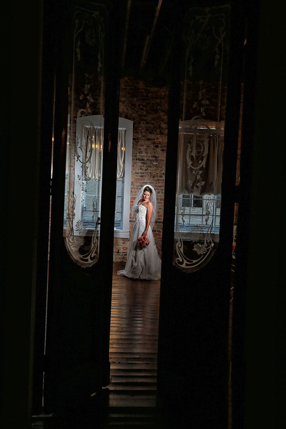 bride posing between two french doors with a bouquet in hand
