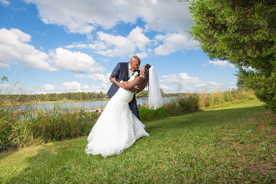 couple posing with groom holding bride in dress