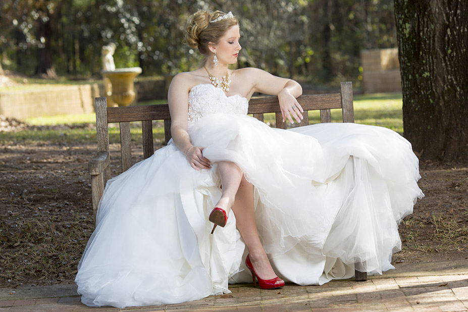 bride posing on a bench with trees in background for wedding photo