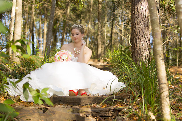 bride posing around trees in dress with flowers in hand