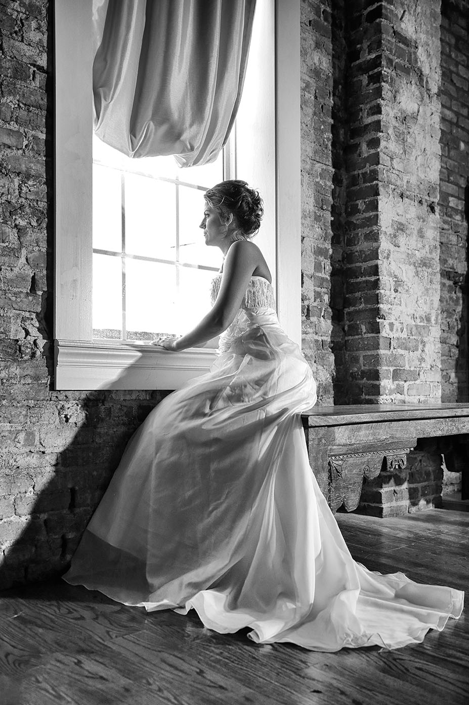 bride posing looking out of a window in wedding dress